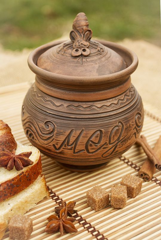 Brown ceramic pot with lid for honey made of red clay.