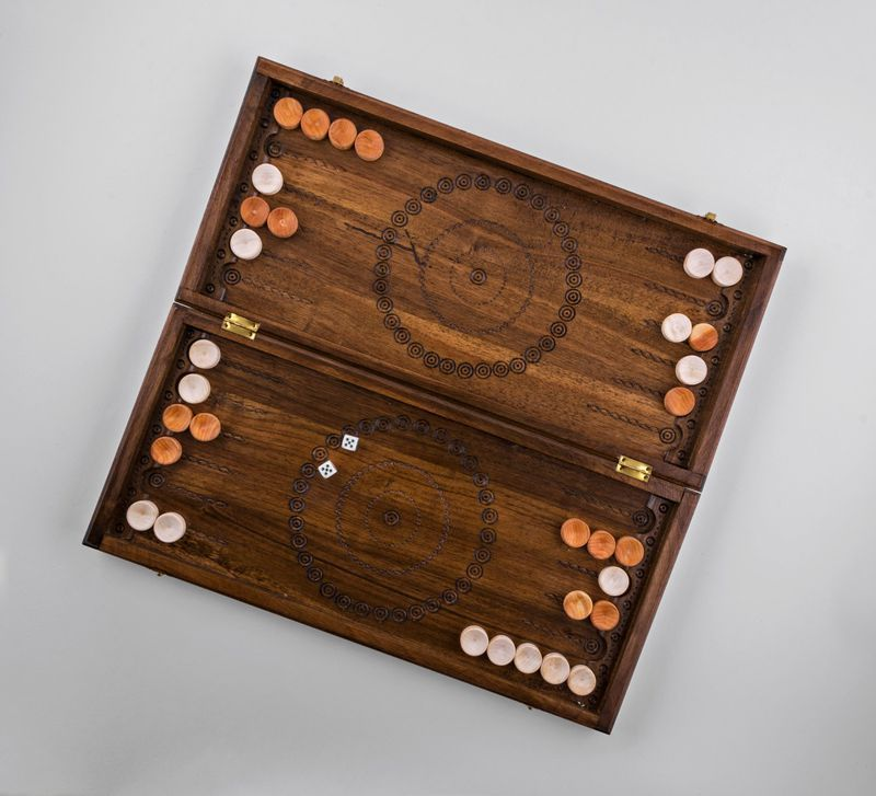 Wooden backgammon with hand carved pattern.