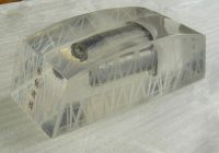 Acrylic/lucite paperweight in bridge shape with metal screw embed
