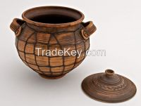 Ceramic pot with lid for cooking made of red clay.