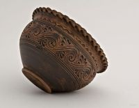 Ceramic brown bowl formed by hand out of red clay.