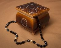 Varnished carved jewelry box inlaid by beads.