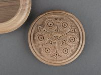 Round wooden jewelry box with hand carved pattern.