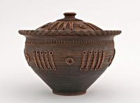 Brown ceramic pot with lid made of red clay.