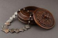 Round figured wooden box with carving and handle.