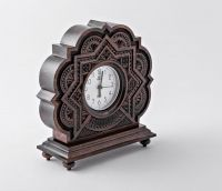 Wooden alarm clock with hand carved pattern.